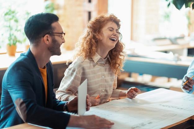 Frau lacht. schöne lockige rothaarige frau lacht bei der zusammenarbeit mit kollegen laugh