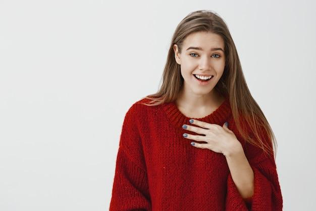 Frau lacht über ungeschickten kerl, der versucht, sie heraus zu fragen. innenaufnahme des freudigen attraktiven populären mädchens im roten losen pullover, scherzend und kichernd, auf sich zeigend, freund über graue wand spöttisch