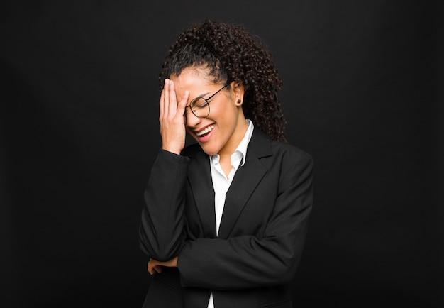 Frau lacht und schlägt auf die stirn, als würde sie sagen, oh! ich habe es vergessen oder das war ein dummer fehler