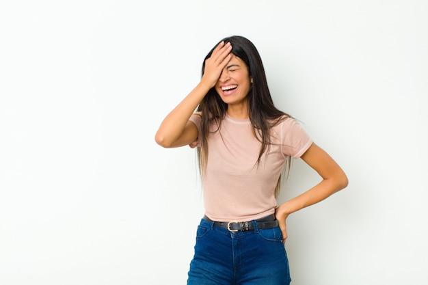 Frau lacht und schlägt auf die stirn