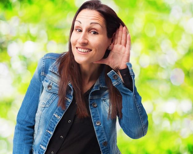 Frau lächelnd mit einer hand auf ihrem ohr