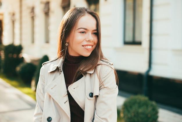 Frau lächelnd schaut weg in einem mantel auf einer herbstsaison