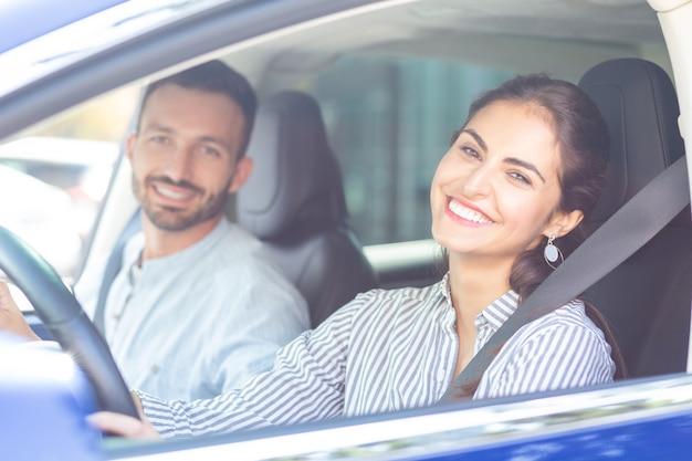 Frau lächelt breit. strahlende frau, die breit lächelt, während sie das auto ihres gutaussehenden bärtigen mannes fährt