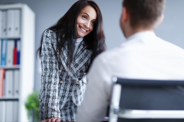 Frau lächelt einen mann an, der im büro steht