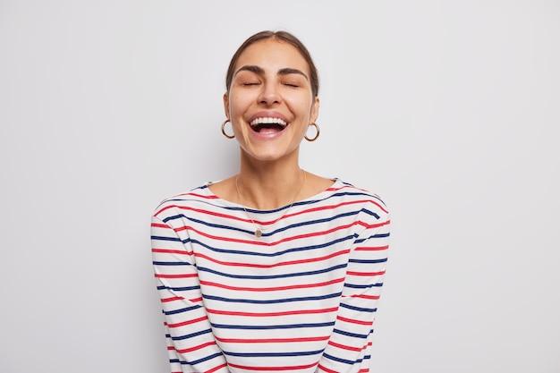 Frau lächelt glücklich drückt positive emotionen aus und lacht über etwas lustiges, gekleidet in lässig gestreiften pullover auf weiß