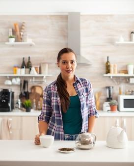 Frau lächelt in die kamera in der küche und hält eine tasse heißen tee während des frühstücks