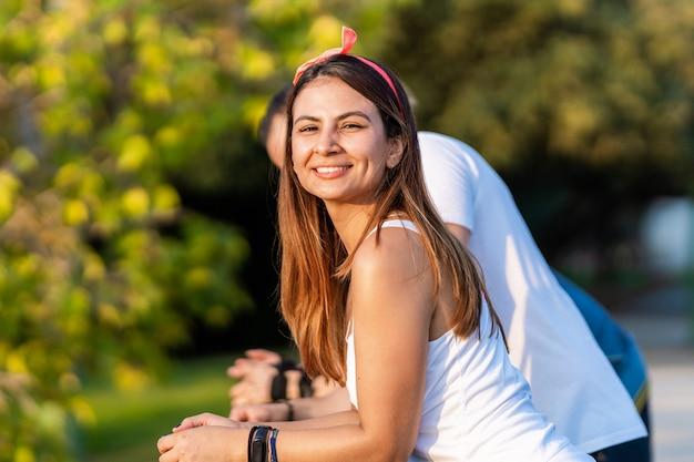 Frau lächelt in die kamera, während sie sich mit ihren freunden auf einem geländer im freien ausruht
