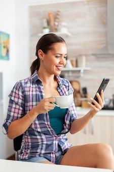 Frau lächelt mit smartphone und genießt eine tasse heißen grünen tee in der küche