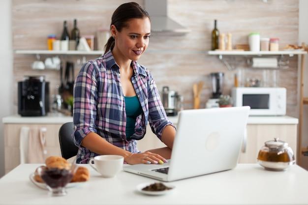 Frau lächelt morgens mit laptop in der küche mit einer tasse heißen grünen tees neben ihr