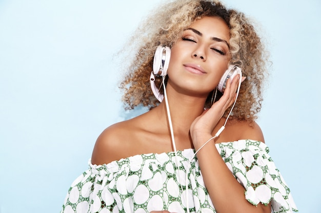 Frau lächelt und hört musik in kopfhörern