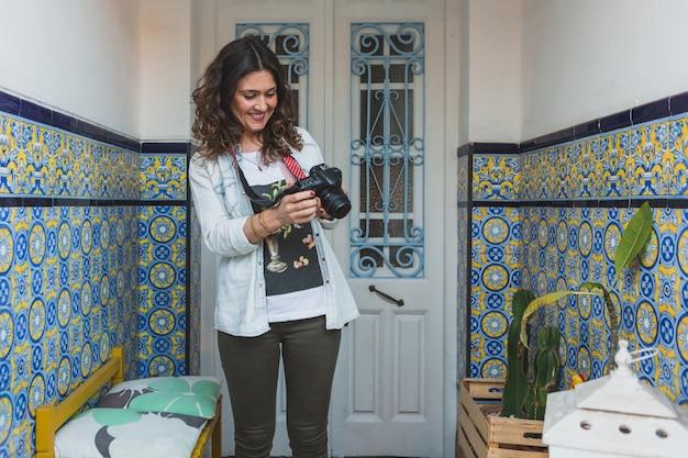 Frau lächelt, während ein paar fotos von ihrer kamera bewerten