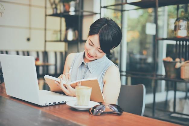 Frau lächelt, während in einer tagesordnung zu schreiben