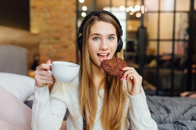 Frau lächelt, während sie kuchen isst, kaffee trinkt und kopfhörer trägt, die mit dem tablet-gadget verbunden sind