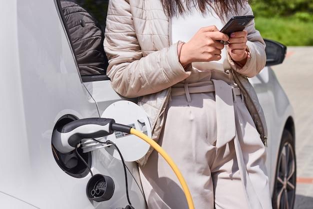 Frau lädt elektroauto auf