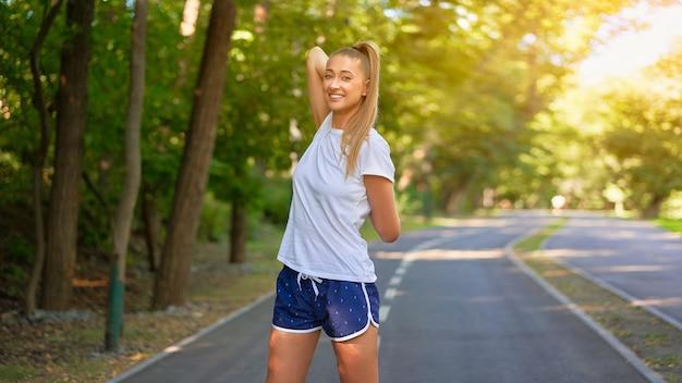 Frau läufer streckt die arme vor dem lauf sommer park morgen mittelalterliche athletische frau, die körper vor dem laufen aufwärmt
