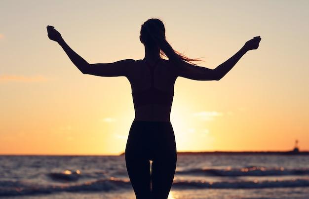 Frau läuft allein in der schönen abenddämmerung am strand