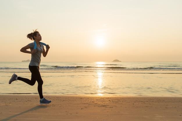 Frau läuft am strand bei sonnenaufgang
