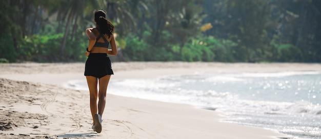 Frau läuft am strand im sommer