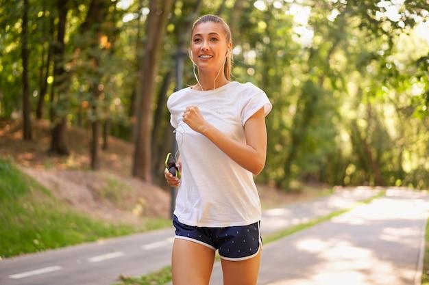Frau läuft asphaltstraße sommerpark aktives sportliches kaukasisches weibliches morgen-training gesundes lebensstilkonzept