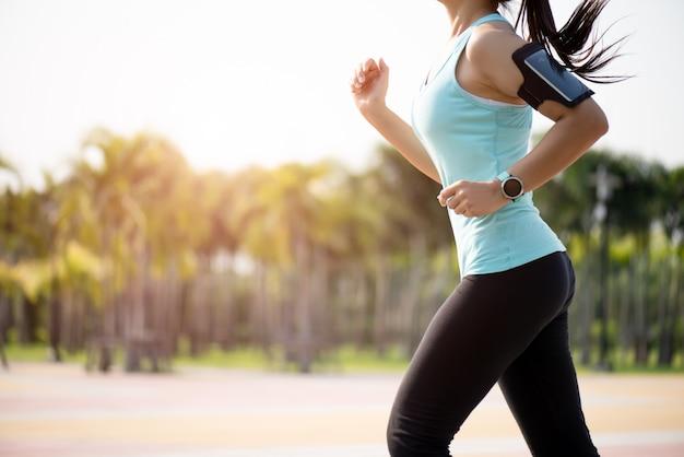 Frau läuft auf der straßenseite zu. schritt, lauf und bewegung im freien
