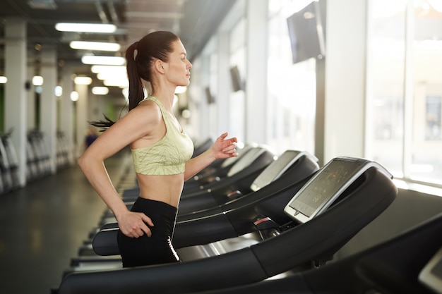 Frau läuft auf laufband im fitnessstudio