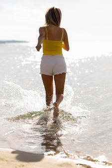 Frau läuft durch wasser am strand