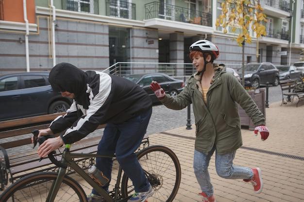 Frau läuft hinter dieb, der ihr fahrrad stiehlt und versucht, den verbrecher zu fangen