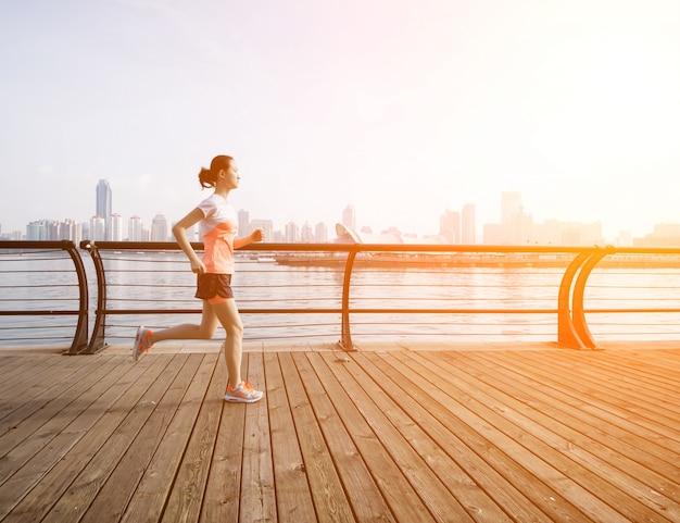 Frau läuft mit dem meer hintergrund