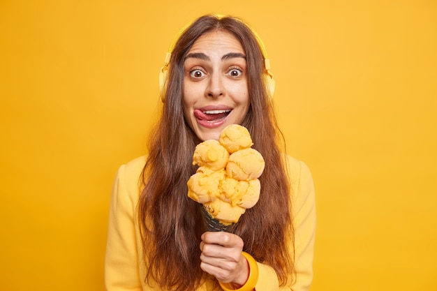 Frau leckt die lippen mit der zunge fühlt die versuchung, leckeres eis in waffel zu essen genießt sommerdessert während des spaziergangs hört musik isoliert auf gelb