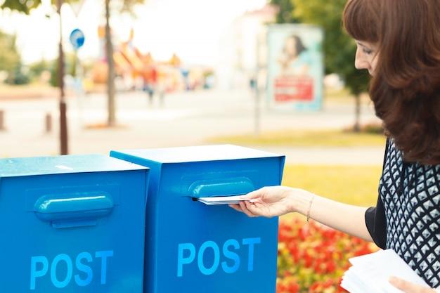 Frau legt briefe in den briefkasten