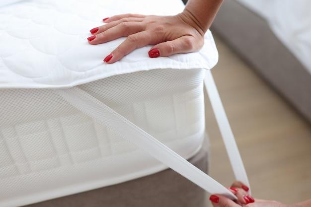 Frau legt decke oder matratzenauflage auf bettspitzen, um das konzept der matratzenauflage zu wählen