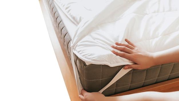 Frau legt den bettbezug oder die matratzenauflage auf das bett oder legt sie zum reinigungsprozess ab