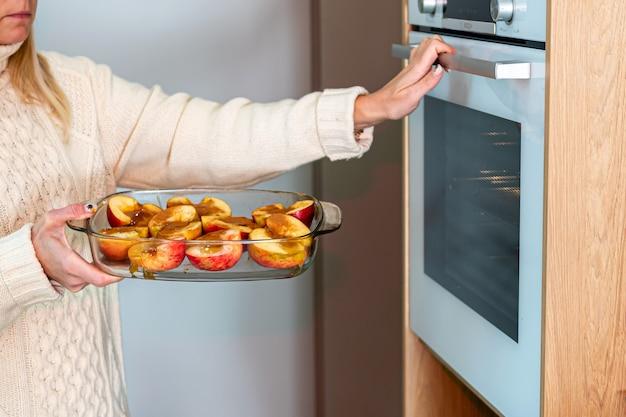 Frau legt glasbehälter mit geschnittenen gefüllten äpfeln in den ofen, hausgemachtes dessertkonzept