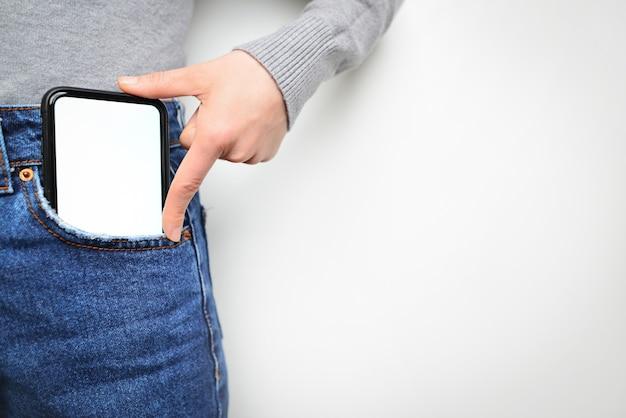 Frau legt handy in jeanstasche auf grauem hellem hintergrund. isolation, platz für text.
