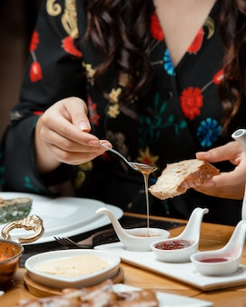 Frau legt honig auf ihr brot im traditionellen frühstücksaufbau