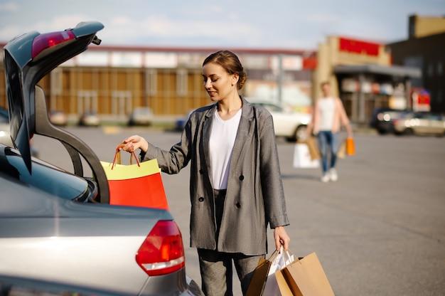 Frau legt ihre einkäufe in den kofferraum auf dem parkplatz