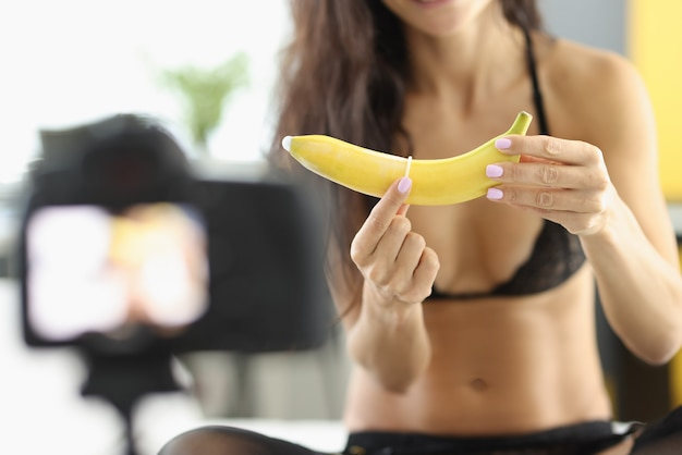 Frau legt kondom auf banane und fängt es mit der kamera ein