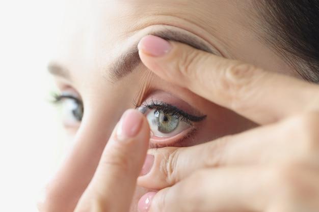 Frau legt regeln für weiche kontaktlinsen für das tragen von kontaktlinsenkonzepten an