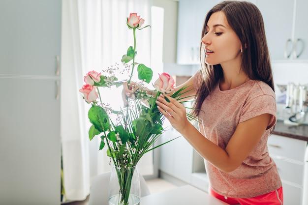Frau legt rosen in die vase. hausfrau, die um gemütlichkeit auf der küche verziert mit blumen sich kümmert.