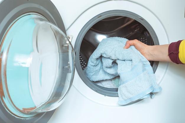 Frau legt schmutzige wäsche in die waschmaschine.