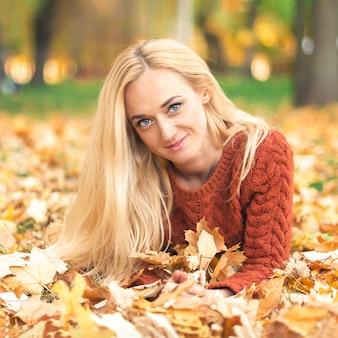 Frau legt sich auf blätter im herbstpark