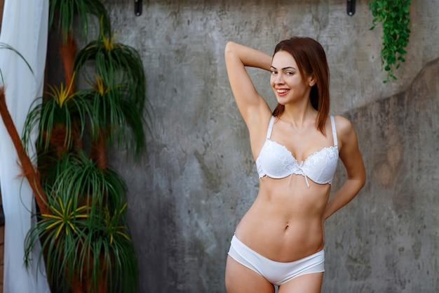 Frau lehnt sich an die betonwand mit grünen tropischen pflanzen herum und posiert in weißem bh und hose