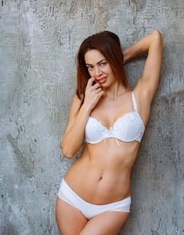 Frau lehnt sich an die betonwand und posiert in weißem bh und hose, während sie den finger an den mund legt.