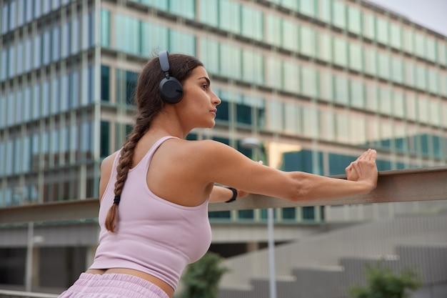 Frau lehnt sich auf schienen, nachdem sie trainiert hat armmuskeln hört audiospur in drahtlosen kopfhörern hat gesunde gewohnheiten posiert in der nähe des modernen glasstadtgebäudes