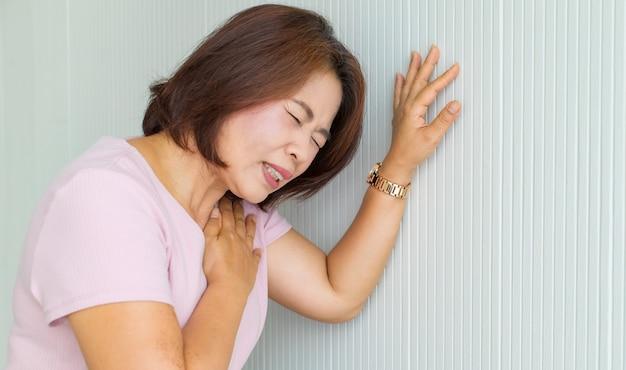 Frau lehnt sich mit schmerzen an die wand, leidet und verzerrt das gesicht und hält sich mit der hand an der brust von herzerkrankungen fest. konzept des st-erhöhten myokardinfarkts.