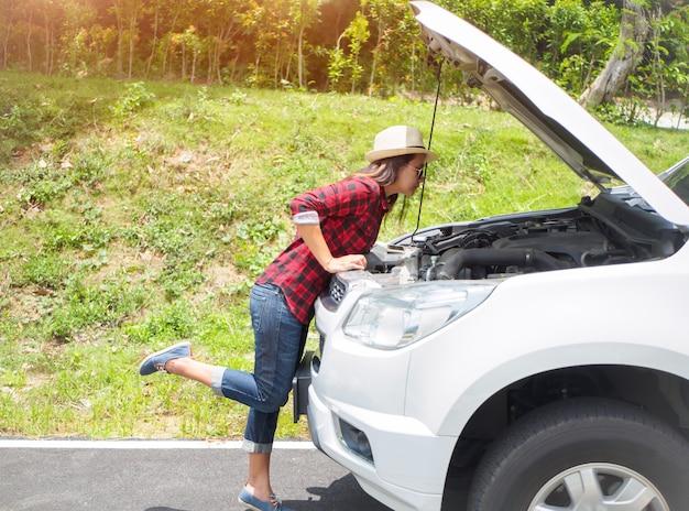 Frau lehnt sich über die überprüfung ihrer automotor nach dem abbau
