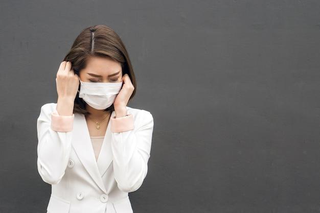 Frau leiden unter kranker und tragender gesichtsmaske, asiatische frau in der schutzmaske, die schlecht sich fühlt