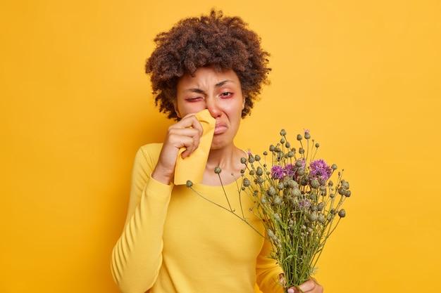 Frau leidet an allergischer rhinitis reibt sich die nase mit serviette hält einen blumenstrauß aus wildblumen fühlt sich unwohl posiert auf leuchtendem gelb
