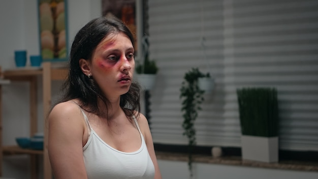 Frau leidet in der küche als opfer von gewalt. gewalttätiger aggressiver mann, der verängstigte, hilflose, verletzliche, ängstliche, geschlagene und in panik geratene frau verletzt, die in terror und druck lebt.