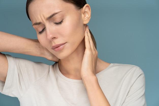 Frau leidet unter chronischen nackenschmerzen, massiert sanft mit den händen und fühlt sich müde